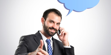 Young businessmen talking to mobile over grey background. © luismolinero - Fotolia.com